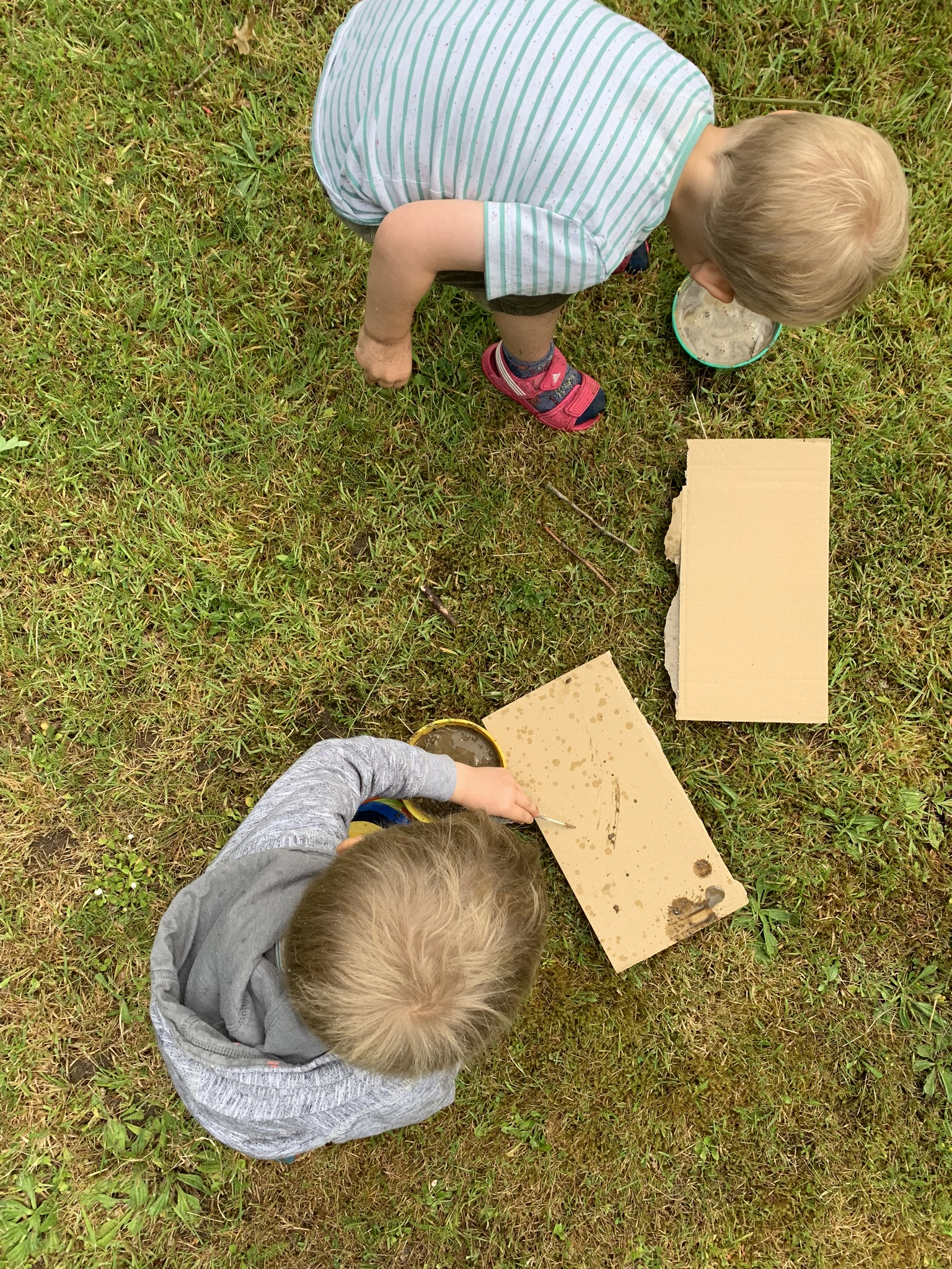 Mud and feather writing, boys do art with mud outdoors