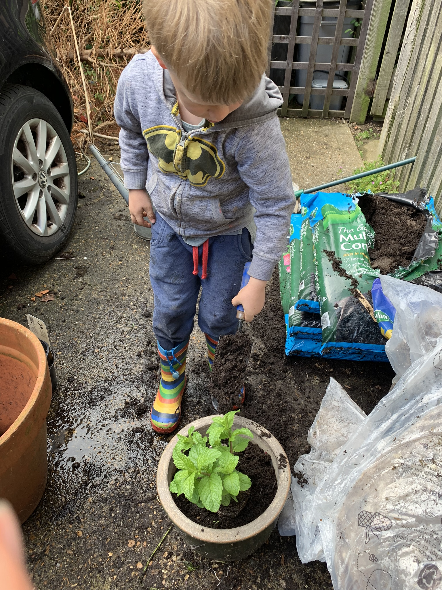 gardening with kids, boy planting flowers in pots